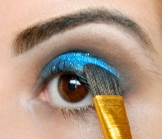 Com um píncel de cerdas sintéticas e um fixador, aplico o glitter azul em toda a pálpebra móvel, por cima daquela sombra azul!